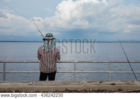 Back View Of Male Fisherman In Camouflage Suit Standing On Pier By Sea And Holding Fishing Rod. Beau