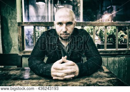 Young Bald Dangerous Gangster Sitting At The Table And Looking In The Camera Intensely. Brutal Membe