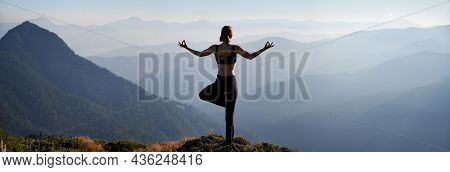 Back View Of Young Woman Performing Yoga Pose On Grassy Hill And Looking At Beautiful Mountains. Spo