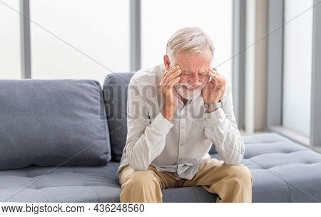 Senior Man Having Headache And Touching His Head While Suffering From A Migraine In The Living Room,