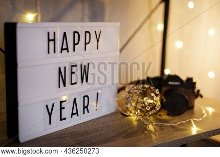 Lightbox With Happy New Year Text On The Table Or Shelf With Vintage Camera And Led Lights