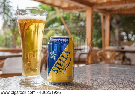 A Glass And A Metal Can Of Stella Beer On The Table In A Beach Cafe. Stella Brand Popular Beer, Prod