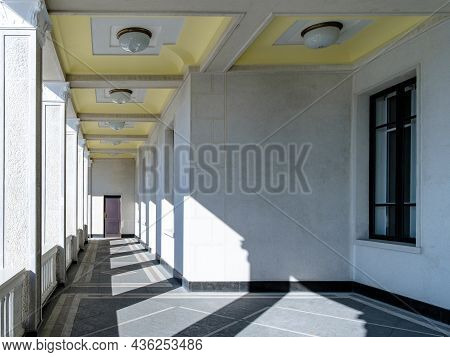 View Of The Columns In The Gallery In An Unknown Building. Bright Sunlight Through The Columns Creat