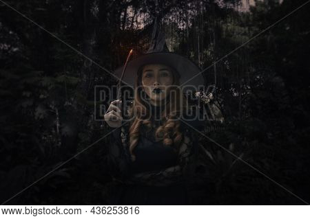 Halloween Witch Holding Magic Wand Standing Over Dark Forest And Tree, Halloween Mystery Concept