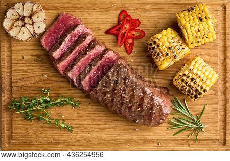 Rare Striploin Roasting. Sliced Juicy And Tender Kansas City Steak. Garlic Clove, Grilled Corn Cob,