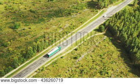 Aerial View Of Highway Road Through Field And Summer Green Forest Landscape. Top View Of Truck Tract