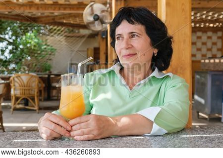 Senior Citizen Brunette Woman Sits At A Table In A Beach Cafe With A Glass Of Fruit Cocktail And Loo