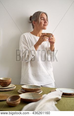 Young Mysterious Girl In A Beautiful Cozy White Muslin Pajamas Stands At With A Cup Of Tea In Hands.
