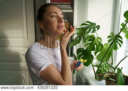 Woman Applying Moisturizing Nourishing Balm To Her Lips With Finger To Prevent Dryness And Chapping