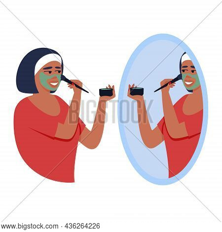 A Woman Applies A Mask To Her Face With A Brush In Front Of A Mirror. Home Skin Care. The Woman Take