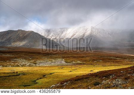 Autumn Tundra And Cold River On The Background Of Misty Snow-capped Mountains