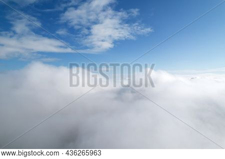 Higher Than Clouds. Aerial Shot Of White Fluffy Clouds And Some Blue Sky In Distance While Flying Ab