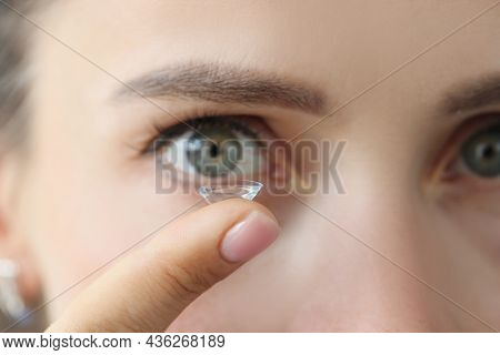 Soft Contact Lens On Female Finger Against Background Of Female Eyes