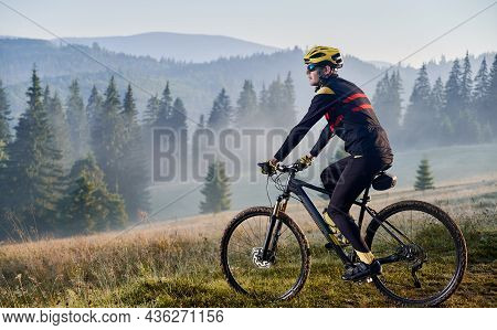 Man Bicyclist Riding His Bicycle In The Mountains In Early Foggy Morning. Side View Of Cyclist Ridin