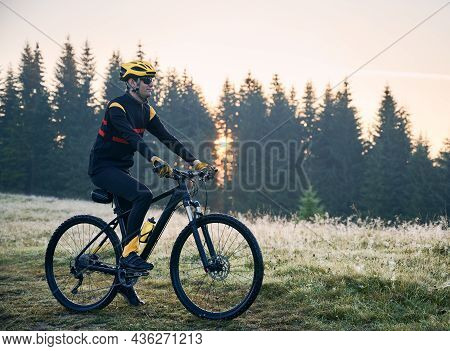 Side View Of Cyclist Standing With Bike On Mountain Trail With Coniferous Trees On Background. Man B