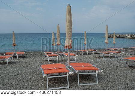 Orange Beach Chairs And Umbrellas On The Pebble Beach Across Beautiful Blue Seacoast Till The Horizo