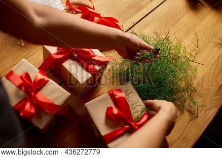 Hands Of Cropped Unrecognisable Woman Packing Christmas Present