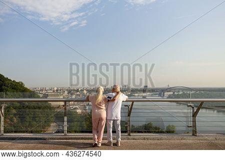 Mature Woman Hugs Man In Sportsweat Leaning Onto Railing On Contemporary Footbridge