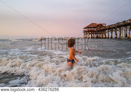 Kid Jumping In The Waves At Sunset. Happy Boy Enjoys Life On Summer Beach. Little Boy In The Spray O