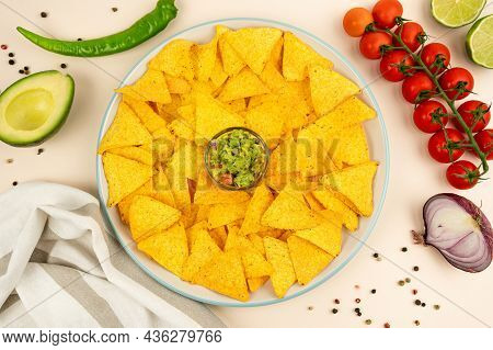 A Delicious Plate Of Tortilla Nachos With Guacamole Sauce, Jalapenos, Red Onions, Tomatoes, Limes, A