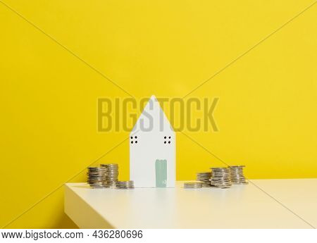 Miniature Wooden House And A Stack Of Coins On A White Table. Real Estate Purchase, Mortgage Concept