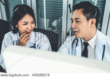 Doctor Team Wearing Headset Talking Actively On Video Call In Hospital Clinic . Concept Of Telehealt