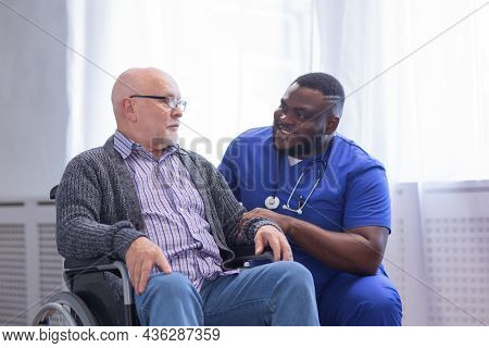 Caregiver And Old Man In A Wheelchair. Professional Nurse And Patient In A Nursing Home. Assistance,