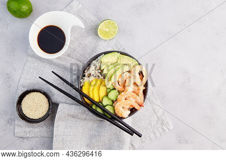 Poke Bowl With Shrimps,, Avocado, Rice, Cucumber, Mango, Pepper And Sesame Seeds, Soy Sauce On Grey
