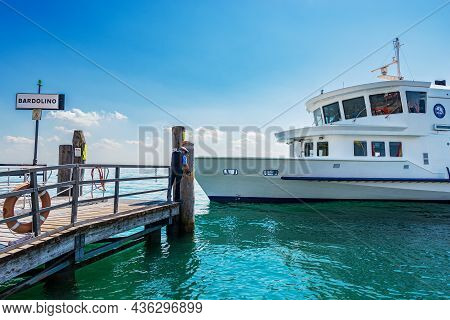 Bardolino, Italy - May 26, 2021: A White Ferry Boat Is Arriving At Ferry Station Of The Small Bardol