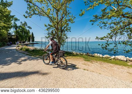 Lazise, Italy - May 26, 2021: Coast Of Lake Garda With A Beach And Bicycle And Pedestrian Lane That