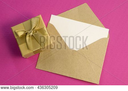 Simple Small Envelope With Space For Writing And Cute Small Rose On Wooden Background With Gold Gift