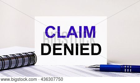 On A Light Gray Background, A Notebook, A Blue Pen And A Sheet Of Paper With The Text Claim Denied.