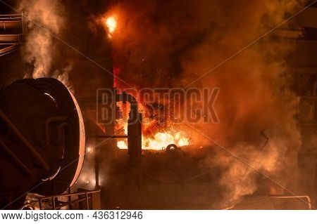 Electric Arc Furnace During Operation. There Is A Lot Of Smoke And Fire.