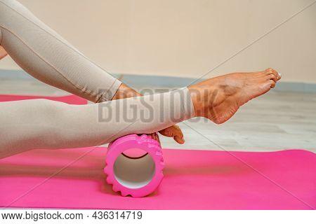 Fit Athletic Women In Beige Sportswear Ride On A Pink Foam Myofascial Massage Roller, Massaging Thei