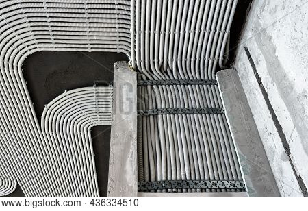 Electrical Cables And Pipes On House Concrete Wall And Ceiling. Modern Plastic Hoses And Conduits Wi