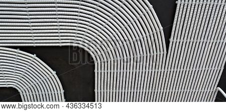 Electrical Cables And Pipes On House Concrete Ceiling, Background. Modern Plastic Hoses And Conduits