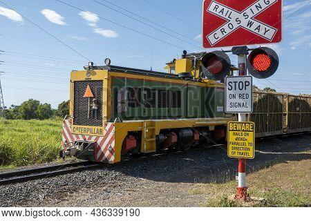 Mackay, Queensland, Australia - October 2021: Train Engine Hauling Filled Chopped Sugar Cane Past Cr