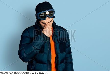 Young hispanic man with beard wearing snow wear and sky glasses tired rubbing nose and eyes feeling fatigue and headache. stress and frustration concept.