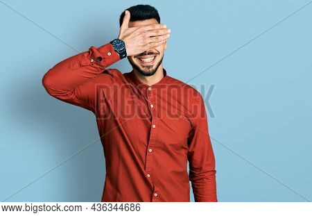 Young hispanic man with beard wearing business shirt and glasses smiling and laughing with hand on face covering eyes for surprise. blind concept.