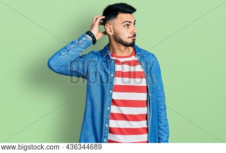 Young hispanic man with beard wearing casual denim jacket confuse and wondering about question. uncertain with doubt, thinking with hand on head. pensive concept.