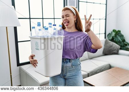 Young redhead woman holding recycling wastebasket with plastic bottles smiling with happy face winking at the camera doing victory sign with fingers. number two.