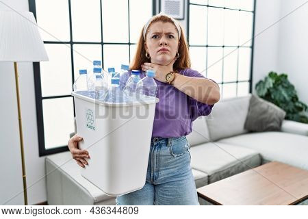 Young redhead woman holding recycling wastebasket with plastic bottles cutting throat with hand as knife, threaten aggression with furious violence