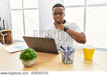 Young african man working at the office using computer laptop cutting throat with hand as knife, threaten aggression with furious violence