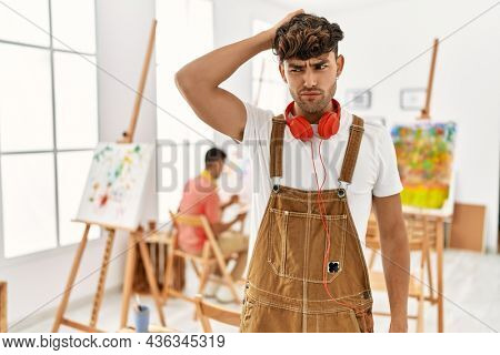 Young hispanic man at art studio confuse and wonder about question. uncertain with doubt, thinking with hand on head. pensive concept.
