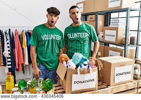 Young gay couple wearing volunteer t shirt at donations stand in shock face, looking skeptical and sarcastic, surprised with open mouth