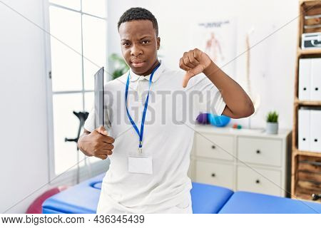 Young african physiotherapy man working at pain recovery clinic with angry face, negative sign showing dislike with thumbs down, rejection concept