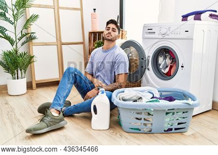 Young hispanic man putting dirty laundry into washing machine relaxed with serious expression on face. simple and natural looking at the camera.