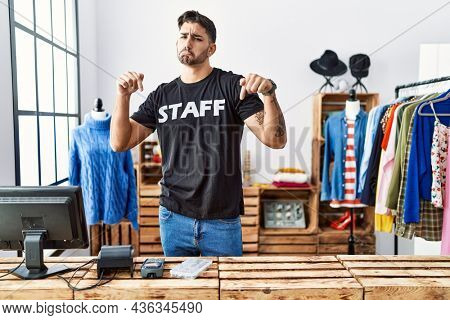 Young hispanic man working at retail boutique pointing down looking sad and upset, indicating direction with fingers, unhappy and depressed.