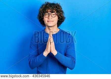Handsome young man wearing casual clothes and glasses praying with hands together asking for forgiveness smiling confident.