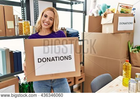 Beautiful blonde woman volunteer holding donations box winking looking at the camera with sexy expression, cheerful and happy face.
